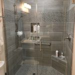 """12"""" x 24"""" tile on the shower walls with a glass and stone mosaic used on the shower floor and border. The frameless glass shower enclosure, stainless steel decorative ADA grab bar and shower corner seat for convenience and safety. Project completed by TWD. #twdaz #bathroomdesign #remodel #generalcontractor #ada #shower www.twdaz.com - My Blog"""
