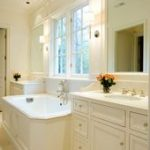 Dreamy bathroom with matching white vanities flanking a drop in spa tub with pan...