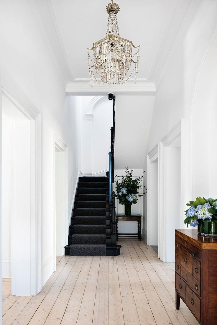 White hallway with black stairs
