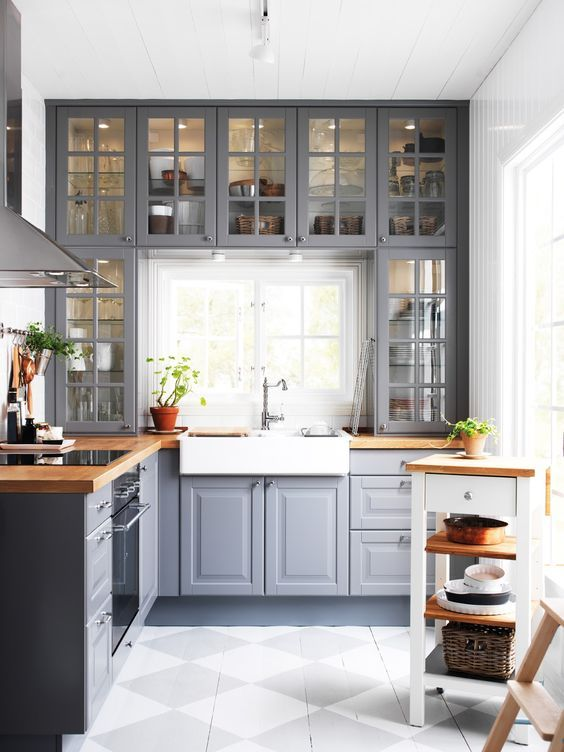 a grey kitchen with wooden countertops and whites and off whites looks tradition…