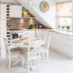 small kitchen with sloping roof in white and small round dining table  #dining #...